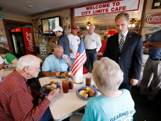 In this June 12, 2018 photograph, Michael Guest, a district attorney and a candidate in the GOP runoff for Mississippi's 3rd Congressional District, speaks with supporters during a campaign rally-lunch in Pearl, Miss. He faces businessman Whit Hughes In the June 26 runoff.