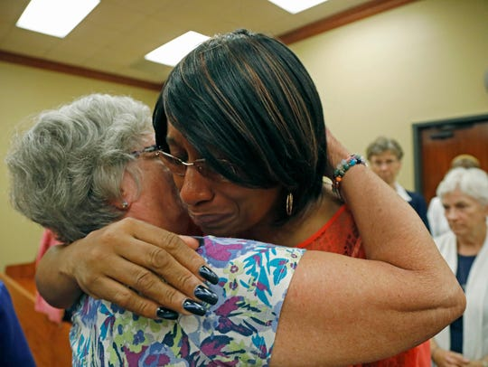 Marie Sanders, the wife of Rodney Earl Sanders, right, hugs various religious women, after her husband pleaded guilty to two counts of murder.