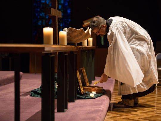 Rev. Jonathan Wickham places a note in a basket during a prayer vigil at All Saints' Episcopal Church on Thursday, June 21, 2018. The vigil focused on migration issues in-light of recent events on the border.