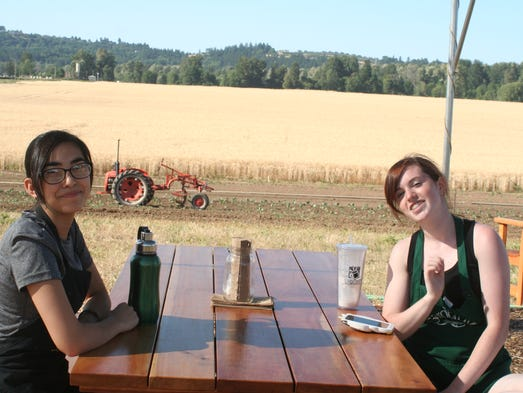 Jazmin Cervantes (left) and Sierra Hurtado, members of the culinary team, relax before starting to cook in the food cart for the Walk with a Farmer event at Minto Island Growers organic farm on July 17.