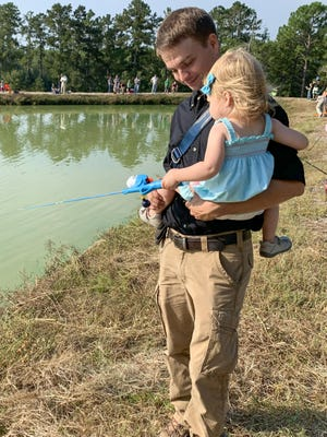 Regional fisheries biologist Jay Payne giving 2-year-old daughter Faye fishing lessons.