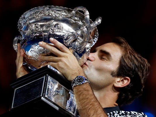 Switzerland's Roger Federer kisses his trophy after defeating Spain's Rafael Nadal during the men's singles final at the Australian Open tennis championships in Melbourne, Australia, Sunday, Jan. 29, 2017. (AP Photo/Kin Cheung)
