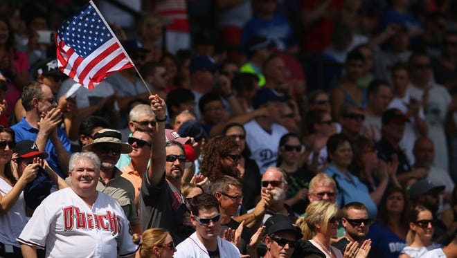 A supporter in the crowd waves an American flag during the game between the Los Angeles Dodgers and the Arizona Diamondbacks at Sydney Cricket Ground.