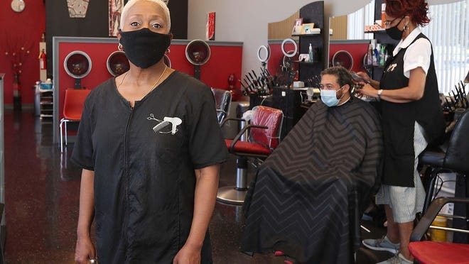 Bobbi Smith, owner of A Beautiful You Hair Studio, stands inside her Wallhaven shop as hair designer Jacque Johnson cuts the hair of client John Salley on June 20 in Akron. The hair studio is one of hundreds of small businesses to receive grants during the COVID-19 pandemic. [Karen Schiely/Beacon Journal file photo]