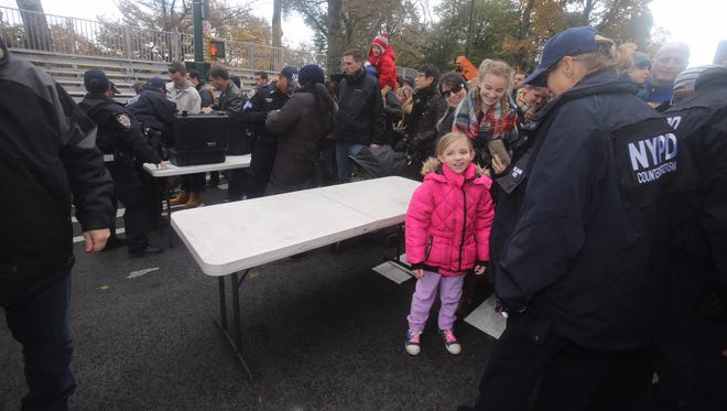 Makenzie Noel, 8, of Clear Spring, Maryland, passes through security on her way to see the Macy's Thanksgiving Day Parade floats being inflated in Manhattan Wednesday, Nov. 22, 2017.