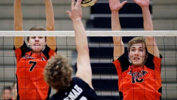 Ryan Frost of Neenah hits as Ryan Tilkens, left, and Ben Brochtrup of Kaukauna go for a block during the Fox Valley Association boys volleyball tournament Saturday at Appleton North High School.