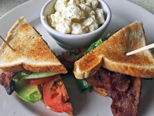Bacon, lettuce, tomato and avocado sandwich with potato salad
