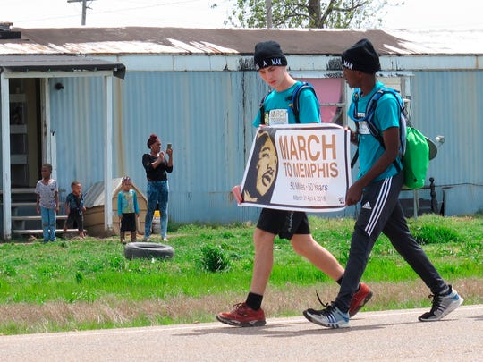 Two teenagers from Mississippi walk along U.S. Highway 61 during a 50-mile march to Memphis, Tennessee, as a tribute to slain civil rights leader Martin Luther King Jr. on Saturday, March 31, 2018, in Dundee, Miss. They are part of a group of six teens who plan to attend events commemorating the 50th anniversary of King's death in Memphis on Wednesday.