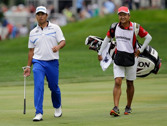 Hideki Matsuyama, left, from Japan, walks with his caddie, Daisuke Shindo, to the 15th green during the final round of the Bridgestone Invitational golf tournament at Firestone Country Club, Sunday, Aug. 6, 2017, in Akron, Ohio. (AP Photo/Tony Dejak)