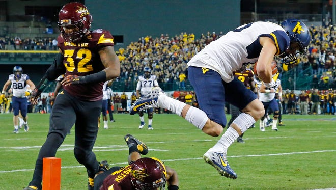 West Virginia Mountaineers quarterback David Sills #15 leaps into the end zone for a touchdown against the Arizona State Sun Devils in the Cactus Bowl Saturday, Jan. 2, 2016 in Phoenix, AZ.