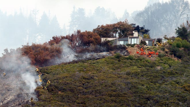 Fire crews work to contain a wildfire in Big Sur, Calif., on Dec. 16, 2013. The fire destroyed dozens of homes and forced about 100 people to evacuate as it chewed through bone-dry vegetation.