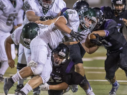 Mission Oak's Isaac Gonzalez (32) tackles Dinuba's