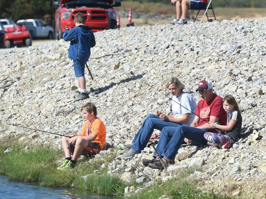 A group fishes from one of rocky banks along the ponds at McCabe Park during the 2017 Kids' Fishing Derby.