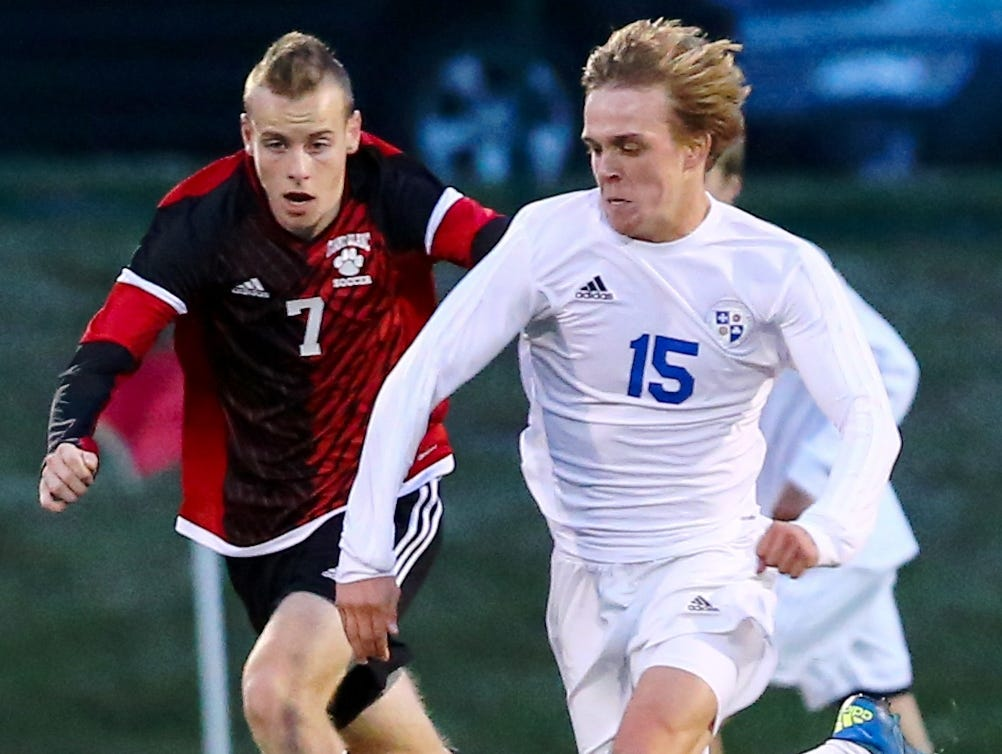 Catholic Central's Cole Moscovic (right) streaks down the field in front of Grand Blanc's Garrett Miller.
