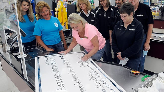 Miller's Hawkins Market manager Karen Graves signs the check for the Neighbors Helping Neighbors $2,521 donation to Associated Charities as Miranda Brown, Chris Box, Diana Cold, Jodi Liggett, Chris Yoke, Keith Searl and Tammy Bragg look on Wednesday.