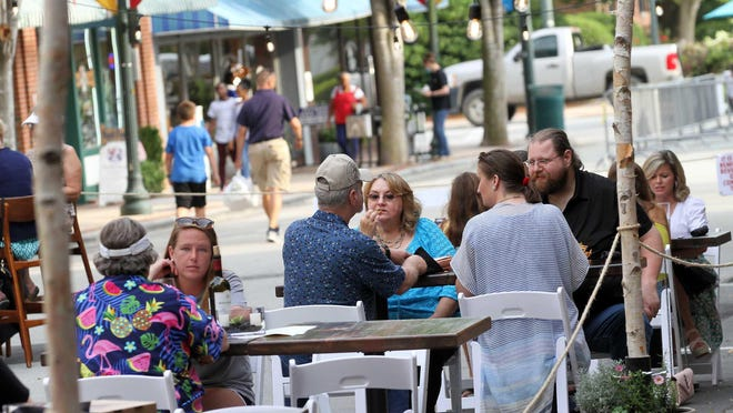 Restaurants and businesses serve patrons and diners at designated outdoor cafe areas in historic downtown New Bern, N.C., May 22, 2020, as part of Phase 2 for reopening businesses. Phase 2 restrictions and guidance provided by state officials require restaurants to operate at 50 percent capacity, space tables at 6 foot apart and have all staff wear masks or face coverings, among other mandates and recommendations concerning the COVID-19 pandemic. Most local restaurants will serve customers at inside and outside tables from 5 p.m. to 11 p.m. on Friday and Saturday evenings throughout Phase 2.