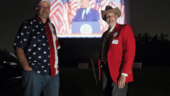 Alternate delegates Gary Click, left, and Jack Etheridge flank the big-screen image of President Donald Trump as the two take part in watching the Republican National Convention at the South Drive-In on Thursday night. Ohio Republicans rented out the theater for supporters to watch Trump accept the GOP nomination for president outside the White House.