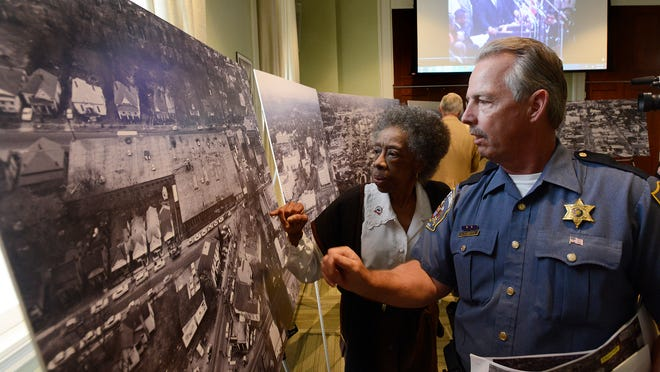 Gwen Patton, left, and Dan Daniel examine large aerial photographs of the Selma-to-Montgomery march in Montgomery as the Alabama Department of Archives and History releases the newly acquired photos and recently discovered film footage, background, of the march and events leading up to it during a ceremony at the archives building in Montgomery on Thursday.