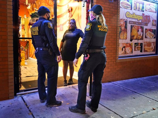 Police officers reminded a woman on the doorstep of a Newark restaurant, New Jersey, of the new curfew and dining rules on Nov. 12 in an area where coronavirus cases recently jumped.