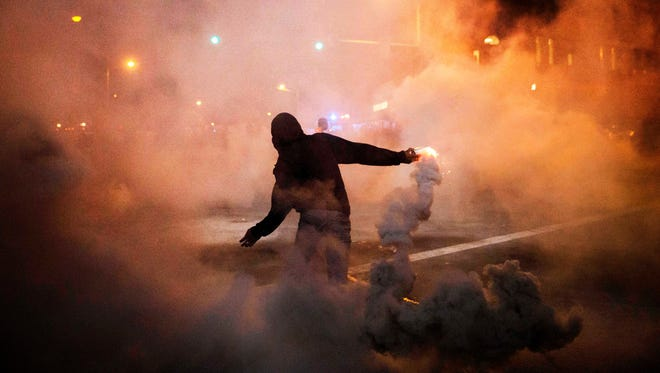 A protester throws a tear gas canister back toward riot police during protests in Baltimore. A 10 p.m. curfew was put in place after Monday's riots.