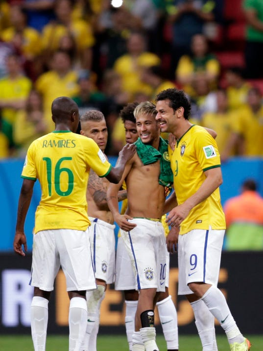 Brazil's Neymar, center, chats with his teammates Fred, right, and Ramires after  a 4-1 win over Cameroon during the group A World Cup soccer match between Cameroon and Brazil at the Estadio Nacional in Brasilia, Brazil, Monday, June 23, 2014. (AP Photo/Dolores Ochoa)