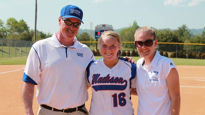 Madison's Michaela Drewnoski, center, along with Patriots softball coaches Andy Gregg and Rebekah Huff.