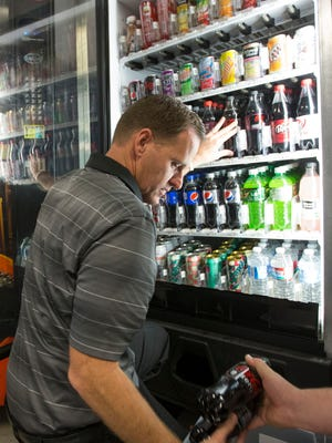 Blind businessman Adam Bevell, left, and his brother-in-law Chris Wennerholm stock a vending machine they own inside the Arizona Capitol Center in Phoenix.