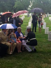 The Burns family is presented with a flag Monday during services at Arlington National Cemetery.