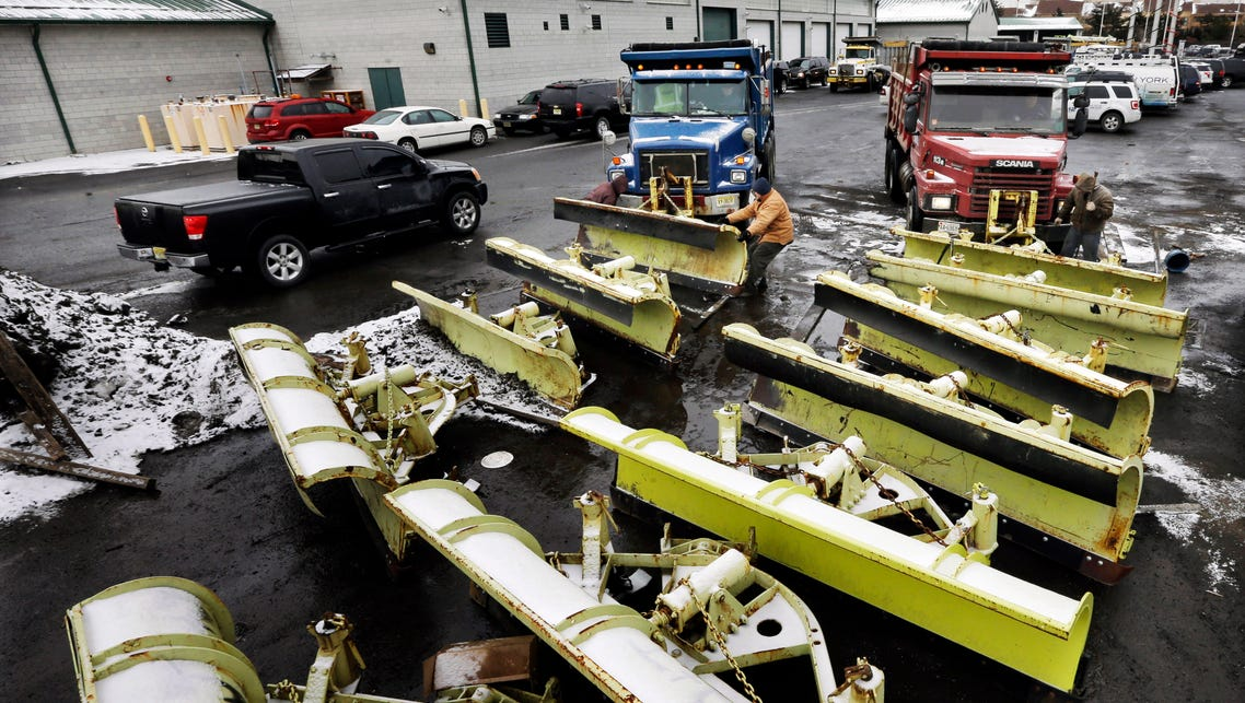 Workers attach snow plows to trucks at a New Jersey