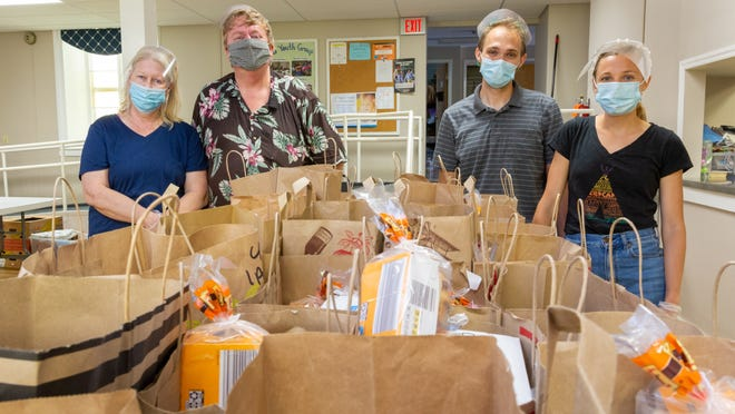 Marti and Steve Mowers and Russell and Lisa Zieman, left to right, pack Summer Curbside Meal Kits to distribute each Sunday at First Presbyterian Church of Victor.