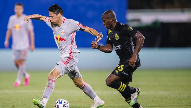 Columbus Crew midfielder Darlington Nagbe challenges New York Red Bulls midfielder Sean Davis for the ball in a MLS is Back Tournament game on July 16, 2020 in Orlando, Florida.