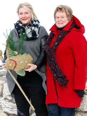 Current sturgeon queen Molly Jaster poses Tuesday with the first sturgeon queen, Carol Groeschl, in front of a frozen Lake Winnebago. Groeschi, 78, was crowned in 1954.