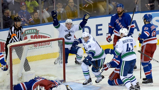 Vancouver Canucks' Alexandre Burrows (14) celebrates his goal against New York Rangers goaltender Henrik Lundqvist, left, with Bo Horvat (53) during the third period of an NHL hockey game Tuesday, Nov. 8, 2016, at Madison Square Garden in New York. The Canucks won 5-3.
