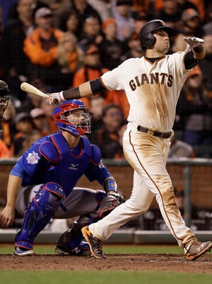 San Francisco Giants' Joe Panik, right, hits a double to score Brandon Crawford in front of Chicago Cubs catcher David Ross during the 13th inning in San Francisco on Monday. The Giants won 6-5 in 13 innings.