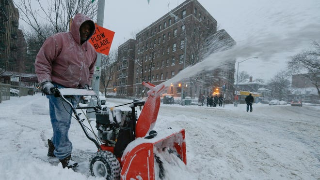 A man uses a snowblower to clear a path Jan. 3, 2014, in New York City.