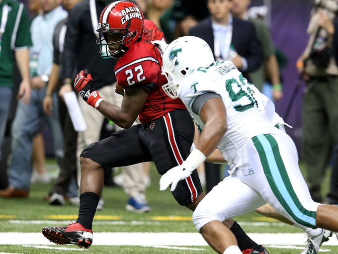 Louisiana-Lafayette running back Elijah McGuire eludes Tulane defensive end Julius Warmsley during a 22-yard touchdown run in the R&L Carriers New Orleans Bowl at the Mercedes-Benz Superdome.