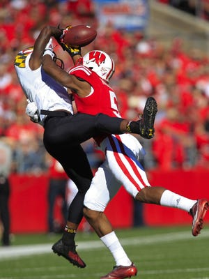 Wisconsin cornerback Darius Hillary (5) breaks up as pass intended for Maryland wide receiver Stefon Diggs (1) during the first half of an NCAA college football game Saturday, Oct. 25, 2014, in Madison, Wis. Hillary was charged with pass interference.