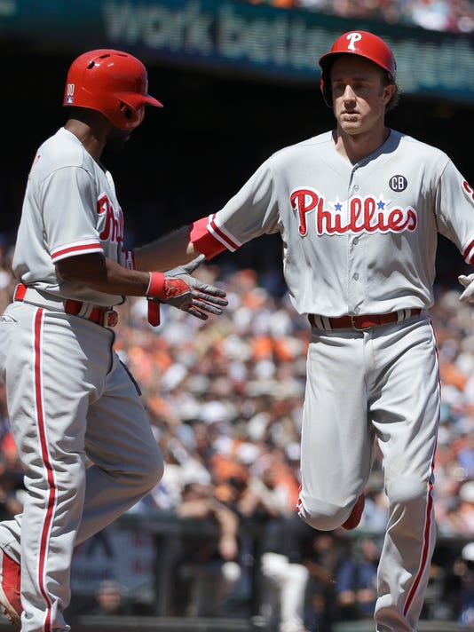 Philadelphia Phillies' Jimmy Rollins, left, and Chase Utley celebrate after scoring against the San Francisco Giants in the fifth inning of a baseball game Saturday, Aug. 16, 2014, in San Francisco. Both scored on a single by Phillies' Ryan Howard. (AP Photo/Ben Margot)