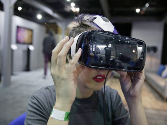 In this March 26, 2015 photo, a woman demonstrates the Oculus virtual reality headset at the Facebook F8 Developers Conference in San Francisco.