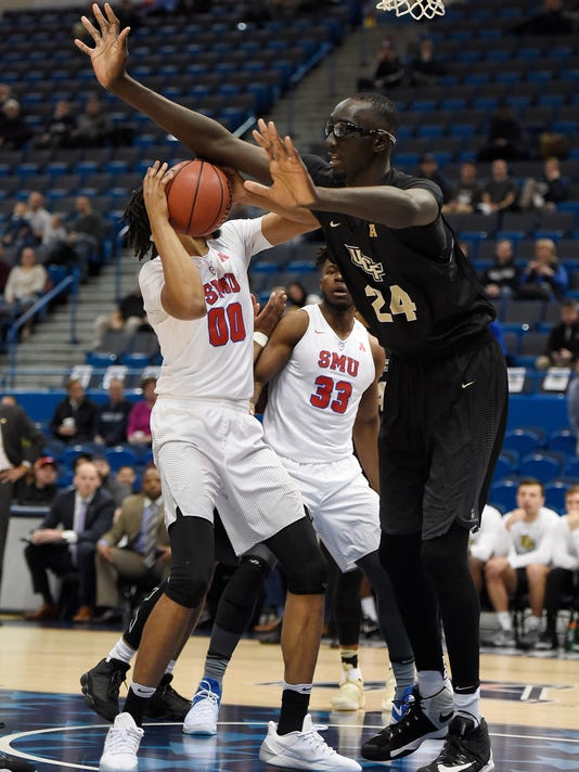 FILE - In this March 11, 2017, file photo, Central Florida's Tacko Fall, right, guards SMU's Ben Moore, left, during the first half of an NCAA college basketball game in the American Athletic Conference tournament semifinals, in Hartford, Conn. The tallest player in college basketball strolls the campus at UCF _ not your traditional basketball power. But anybody in the NBA or college hoops who doesn't know 7-foot-6 Tacko Fall should get up to speed on the 21-year-old from Senegal. (AP Photo/Jessica Hill, File)