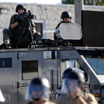 A police tactical team moves in to disperse a group of protesters in Ferguson, Mo., on Aug. 9.