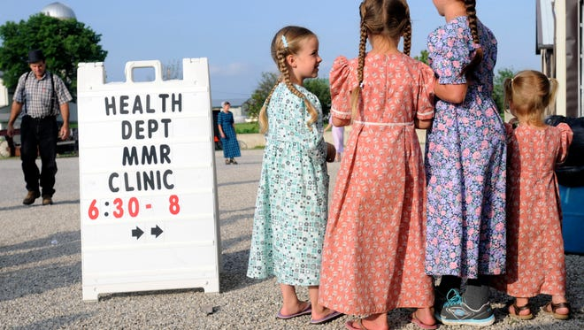 In this June 25, 2014 photo, young Mennonite girls gather outside a health clinic offering measles, mumps and rubella vaccinations in Shiloh, Ohio.