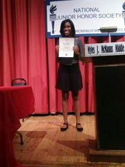 Shanell Holmes proudly displays her McManus Chapter of National Junior Honor Society certificate.
