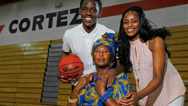 Cortez High basketball player Christian Hakilimali poses with his mother Jacky Mukamazera and sister Solange Mukantabana on Monday, Feb. 2, 2015, in Phoenix.