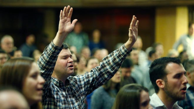 Steve Fickess of West Irondequoit raises his hands during a service at Grace Road Church in the Auditorium Center.