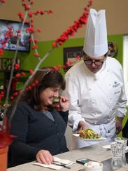 Chef Tamas Ronyai serves up a savory roasted chicken waffle to Debbie MacLeod during a recent lunchtime.