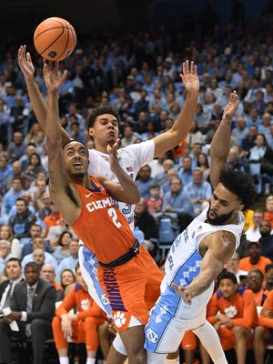 Clemson guard Marcquise Reed (2) shoots past North Carolina guards Cameron Johnson (13), center, and guard Joel Berry II (2) during the 2nd half on Tuesday, January 14, 2018 at UNC's Smith Center in Chapel Hill, N.C.