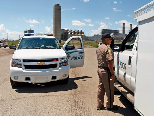 Navajo Nation Police Officer Rodney Harrison speaks with a motorist Monday near the entrance of the Four Corners Power Plant in Waterflow.
