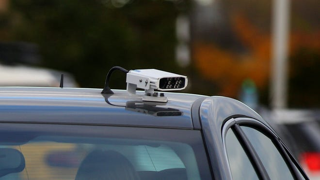 Patty Parsons, with MCC parking enforcement department uses license plate readers mounted on the roof of her car to scan for illegal parkers in the Brighton campus' parking lot.