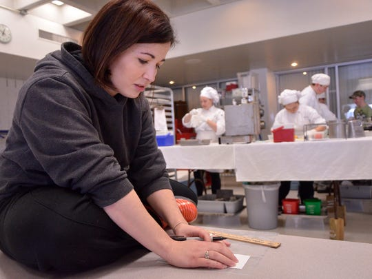 Diana Woodward, instructor/coach of the Plymouth-Canton Educational Park Hospitality and Culinary Arts program, takes notes while students prepare for a competition.